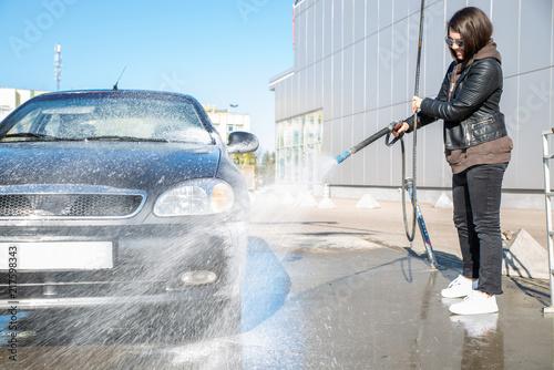 young woman washing car at self-service carwash