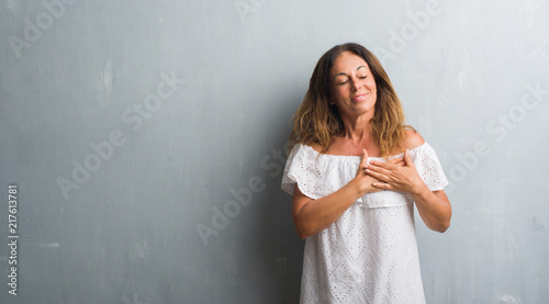 Leinwandbild Motiv Middle age hispanic woman standing over grey grunge wall smiling with hands on chest with closed eyes and grateful gesture on face. Health concept.