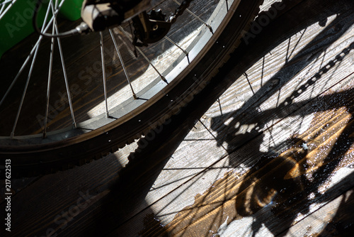 Rear wheel of a cycle with the chain and gear cogs in reflected shadow with a puddle of water creating an art reflection - 217622513