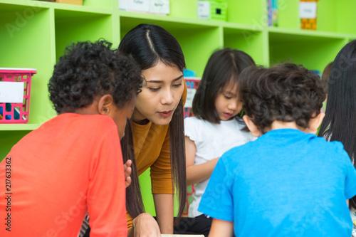 Foto Murales Asian female teacher teaching mixed race kids reading book in classroom,Kindergarten pre school concept.