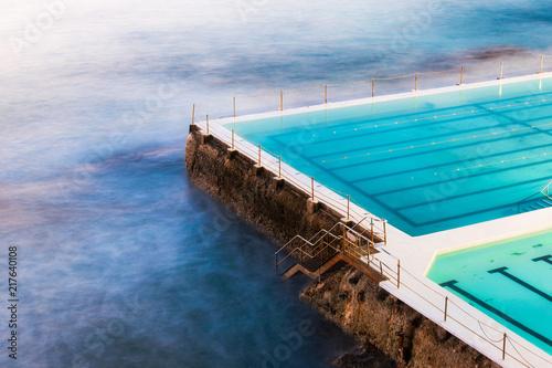 Foto Murales The edge of empty rock pool towards the ocean.
