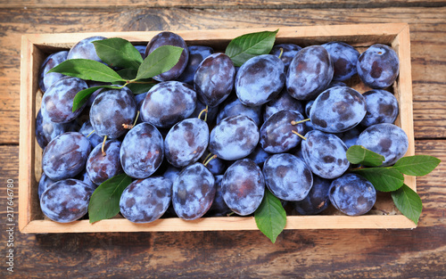 Foto Murales blue plums in wooden box, top view