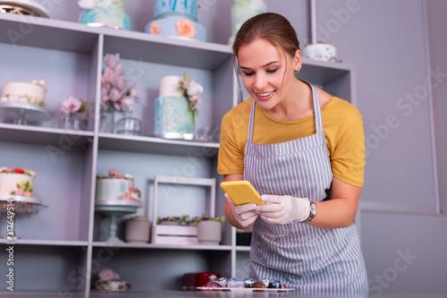 Foto Murales Yellow phone. Beautiful cheerful woman holding her yellow phone while making photo of chocolate