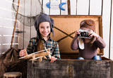 two little girls-pilots in big wooden chest playing camera and wooden plane - 217656103