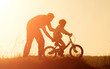 Silhouette of father teaching little daughter to ride a bike at meadow during sunset. Caring father teaches her daughter to ride bicycle