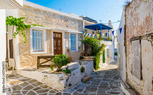 Foto Murales Small narrow street of Greek village of Lefkes with houses made of stone with small yard outdoors, Paros island