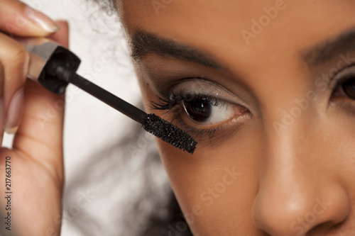 Foto Murales portrait of a young dark-skinned woman applying mascara on a white background