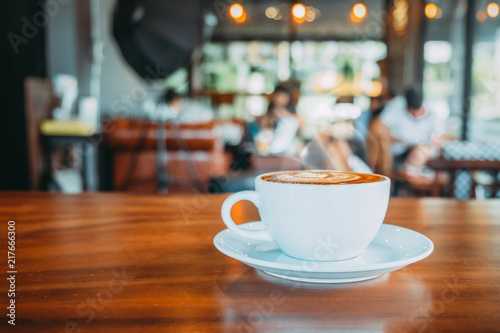 Wall mural White cup of hot coffee on table in cafe with people. vintage and retro color effect - shallow depth of field