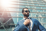 Bearded businessman wears blue suit and sunglassesbefore modern building - 217678308