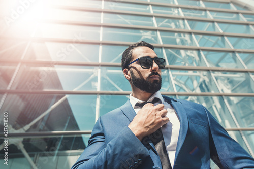 Bearded businessman wears blue suit and sunglassesbefore modern building