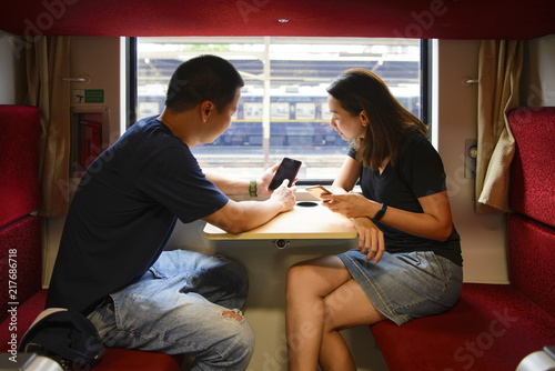 Young tourist man and woman using on the phone on train while travel