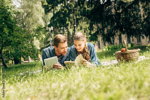 Leinwanddruck Bild beautiful young couple lying on grass at park with tablet and book