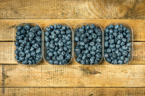 Foto Murales Juicy and blueberries in a container on an old wooden table in the summer
