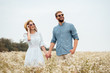 Leinwandbild Motiv portrait of happy lovers in sunglasses holding hands in field with wild flowers