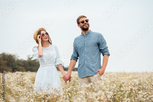 Leinwanddruck Bild portrait of happy lovers in sunglasses holding hands in field with wild flowers