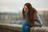 Young lonely and depressed woman is sitting in grief.  - 217704784