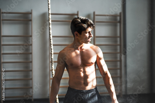 Foto Murales Fit young man in gym standing topless in front of a climbing rope.
