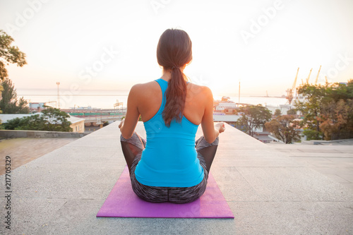 Wall mural Young woman practicing yoga on the beach