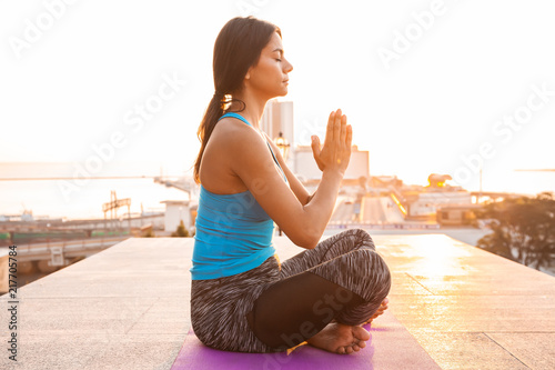 Plexiglas Zen Young woman practicing yoga outdoors. Harmony and meditation concept