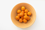 Top down view of orange mandarines in bamboo bowl on white table