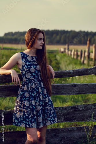 beautiful teenager girl with long healthy hair in blue dress relaxing on sunset evening in farm on summer time.