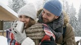 Loving young man smiling and embracing his beautiful girlfriend while she drinking hot tea from metal mug in forest at snowy winter day - 217711939