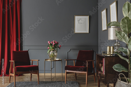 Foto Murales Two burgundy armchairs placed in grey living room interior with red drape. molding on the wall with posters, fresh flowers in glass vase and wooden cupboard