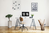 Real photo of a simple home office interior with a desk, chair, plant, computer, poster and wall organizer - 217715753