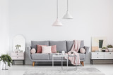 Real photo of an elegant living room interior with a grey sofa, pink pillows, cabinets and lamps