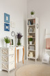 Real photo of wooden rack with books and decor, posters on wall and lavender in glass vase standing on console table