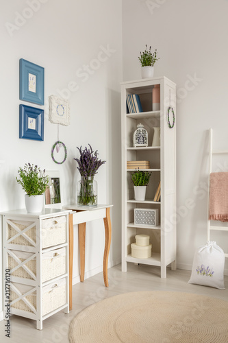 Real photo of wooden rack with books and decor, posters on wall and lavender in glass vase standing on console table - 217716120