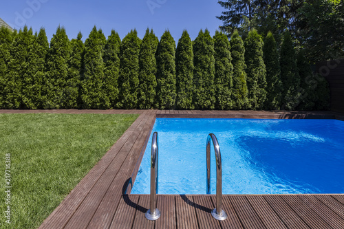 Foto Murales Swimming pool in the garden with trees and green grass during summer. Real photo