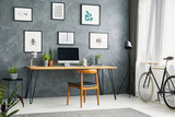 Bicycle in a grey home office interior with a wooden desk and chair, graphic collection and computer with an empty screen. Place your product - 217716592