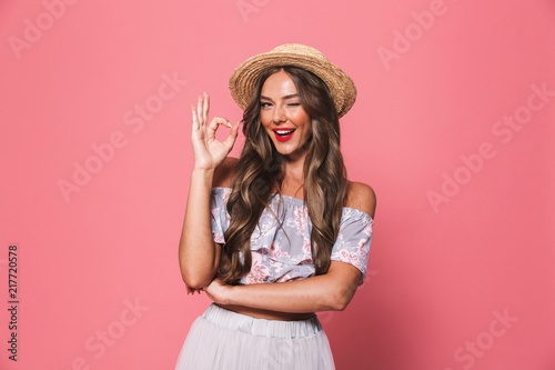 Leinwanddruck Bild Portrait of beautiful european woman 20s wearing straw hat winking and showing ok sign, isolated over pink background in studio