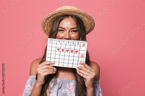 Leinwanddruck Bild Portrait of beautiful european woman 20s wearing straw hat holding period calendar, isolated over pink background in studio