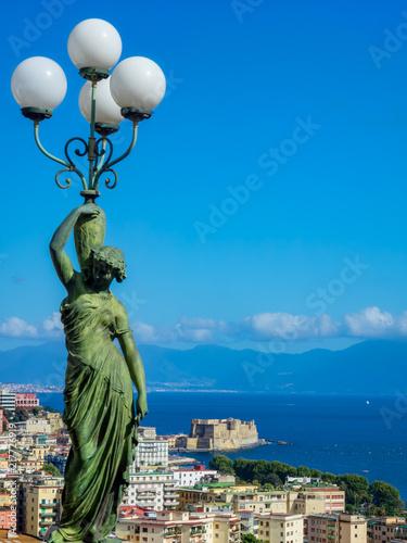 Fotobehang Napels Vue sur la baie de Naples avec une statue de bronze qui porte une amphore doté de quatre lampadaires blancs au premier plan