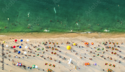 Aluminium Beige Aerial view of a beach with colorful umbrellas, people swimming in the sea, sunny day. Drone landscape from above