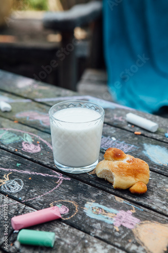 Foto Murales A glass with milk and a homemade bun on a wooden table painted with crayons