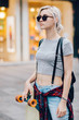 Portrait of young hipster woman with skateboard