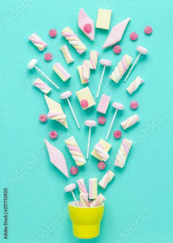 marshmallows i lolly pops wybuchające z żółtej filiżanki, jasny pastelowy motyw