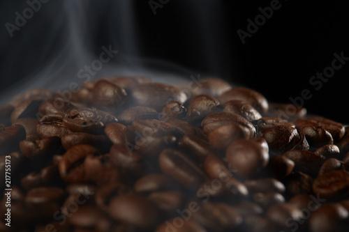 Foto Spatwand Koffiebonen grains of coffee with smoke on a dark background