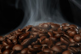 grains of coffee with smoke on a dark background