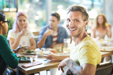 Happy guy with toothy smile turning for camera while sitting by sersved table among his friends