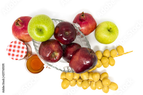 Foto Murales Rosh Hashanah (Jewish New Year) Traditional Symbols, Honey in a glass jar, Pomegranates, Dates, Red And Green Apples. Isolated On A White Background