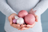 christmas balls. elegant festive decor and new year holiday ornaments concept. man holding rose gold glittery baubles in hands.