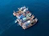 Aerial view of a large number of fishing trawlers operating together illegally in a marine reserve - 217781554