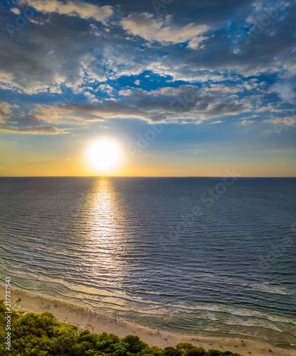 Foto Spatwand Strand Ein wunderschöner Sonnenuntergang über dem Meer mit weißen Sand von Strand im Vordergrund als hochkant Panorama als Aerial, Luftbild, die Ostsee von ihrer schönsten Seite