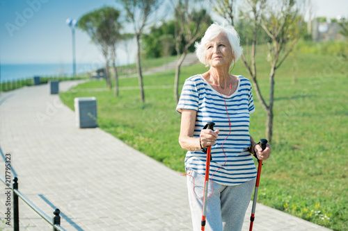 Portrait of active senior woman practicing Nordic walking with poles outdoors in park, copy space - 217795323
