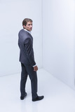 serious businessman standing in corner - 217797548