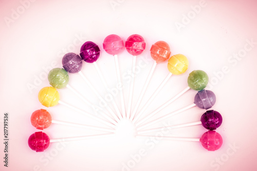 Foto Murales Rainbow design of sweet colorful lollipops against white background with vintage retro tone